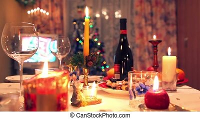 Decorated christmas dining table with bottle, glasses, candy, candles