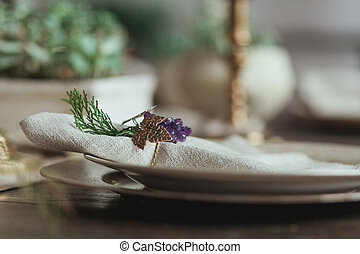 Decorated Christmas Dinner Table Setting of empty dish and sackcloth rustic napkin with decor ring in the form of grapes