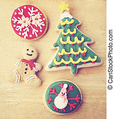 Decorated christmas gingerbreads on wooden background with retro