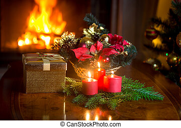 Decorated Christmas table at living room with burning fireplace
