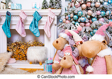 Decorated Christmas tree. Christmas mooses or deers. Many balls on the tree for the new year. Stockings on the fireplace waiting for Santa Claus.