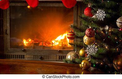 Decorated Christmas tree next to burning fireplace with natural logs