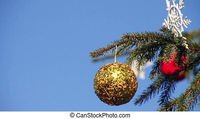 Decorated Christmas tree on background blue sky.