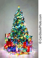 Decorated Christmas tree with colorful lights surrounded by presents.