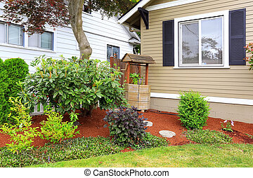 House with front yard landscape and decorated draw well in the corner