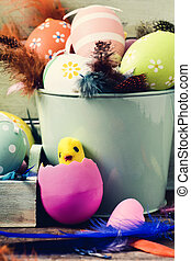 decorated easter eggs, feathers and toy chick