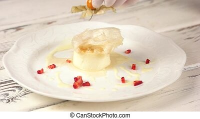 Decorated flan on plate. Hand holding physalis flower.