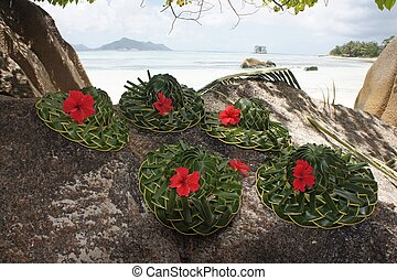 decorated hats from palm leaf with red flower