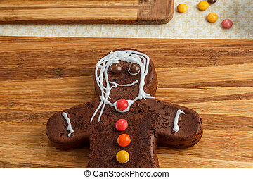 Decorated homemade gingerbread man for Christmas on wood