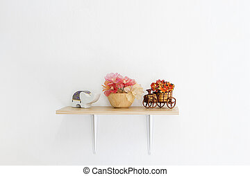 Decorated interior on shelf, put flower, wooden bowls and elephant made of ceramic