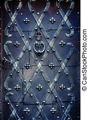 Decorated iron door - Old, solid, black door with the grille...