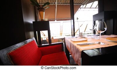 Decorated table for two with glassware and red chairs stand in a restaurant lounge