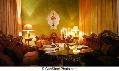 Decorated table stands among sofas and two floor lamps