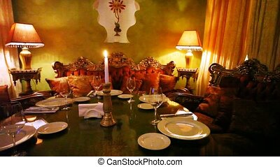 Decorated table with candle stands surrounded with sofas