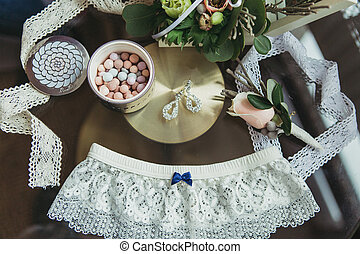 decorated wedding bouqet near garter and boutonniere on...