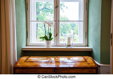 white orchids and white canlde standing on the windowsill of a white window with a brown trunk in the foreground