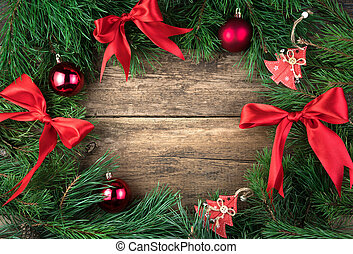 Decorated with red Christmas toys, bows and glass balls, a pine branch on a natural wooden background.