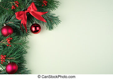 Decorated with red Christmas toys, bows and glass balls, pine branches on a light green background.