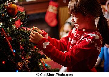 Decorating Christmas tree - Little girl decorating Christmas...