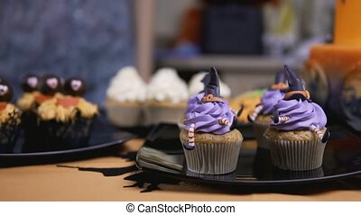 Decorating cupcake with icing hat and legs. Muffin like witch. Halloween concept