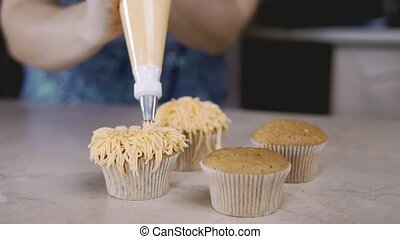 Decorating cupcake with orange cream. With cooking bag confectioner make muffin