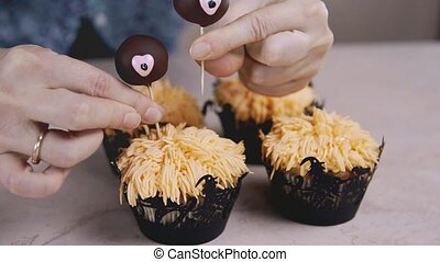 Decorating funny cupcake with chocolate eyes. Muffin with Halloween concept