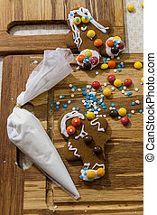 Decorating gingerbread man for Christmas on wooden table