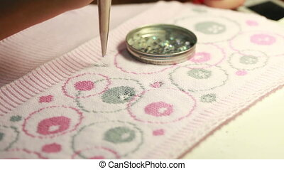 Decorating knitted tissue by sequins, close-up