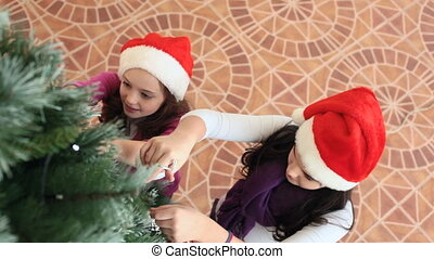 Decorating New Year tree - Two girls decorating fir-tree ...