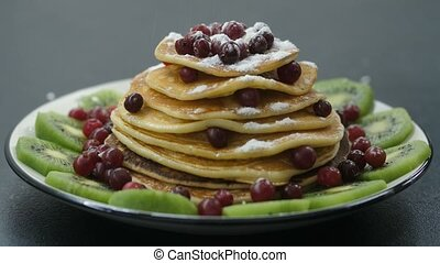 Decorating pancakes with berry and powdered sugar - Close-up...
