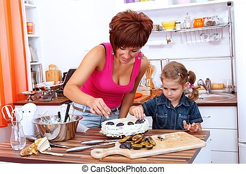 Decorating the cake - Girl helps her mother decorating the ...