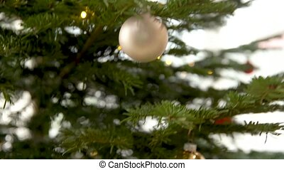 decorating the Christmas tree with silver glass balls