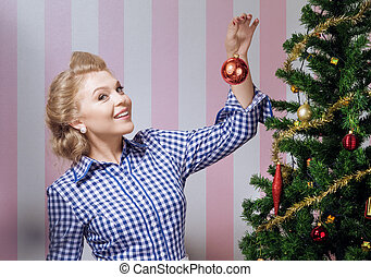 decorating tree - portrait of nice young woman hanging...