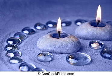 Decoration background. Candles and glass drops on sand. Blue...