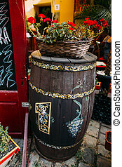 Decoration fragment of sidewalk summer restaurant in Lviv, Ukraine. Decorative wooden barrel with red flowers on it
