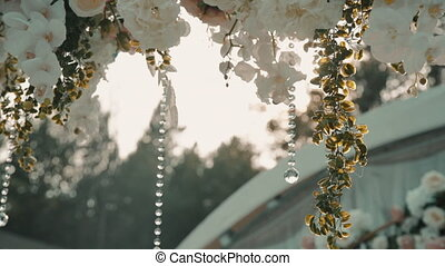 Decoration of event with flower, beads in outdoor. Clusters of buds and chain of transparent ball hang in background of garden. Sunlight illuminates beautiful summer decorations in park at top. White and pink platinum and natural details on wood.