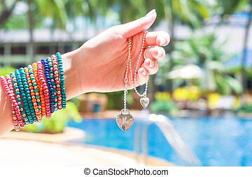 Decoration pendant in hand over the pool at tropical resort...
