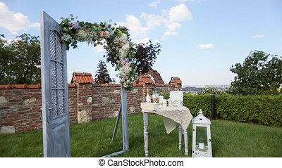 Decorative arch, table and lamp with flowers at a wedding ceremony outdoors
