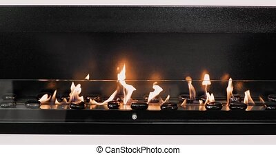 Decorative artificial fireplace with black stones in room...