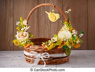 Decorative basket decorated with flowers on a wooden background