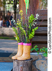 Decorative bouquet of flowers in Boots on wooden background