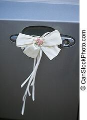 Decorative bow on car handle for wedding decor.
