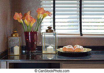 decorative candle set with brass glass lamp and beautiful flowers on the table at home