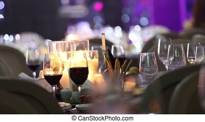 Decorative candles on the dining table, glasses and Christmas candles on the table