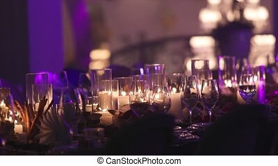 Decorative candles on the dining table, glasses and Christmas candles on the table, white wax candleswith glass candlestick, Candle with Glass Candlestick, restaurant, interior, close-up