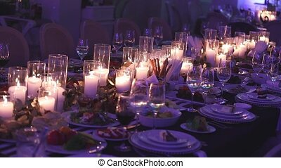 Decorative candles on the dining table, glasses and Christmas candles on the table, white wax candleswith glass candlestick
