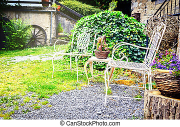 Decorative chairs in summer backyard garden