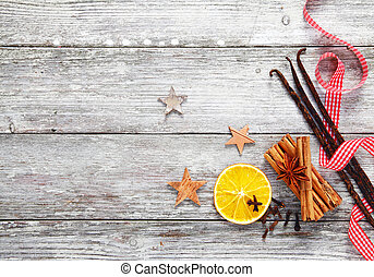 Colourful array of decorative Christmas spices with a fresh red and white checked twirled ribbon on a background of grungy textured weathered white wood