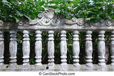 Decorative concrete fence against a background of green plants in summer.