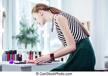 Beautiful nice woman looking at her cosmetics